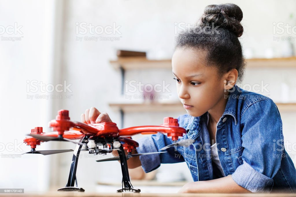 Little girl child playing with drone at home stock photo