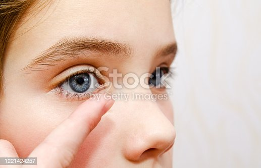 istock Little girl child putting contact lens into her eye closeup 1221424257