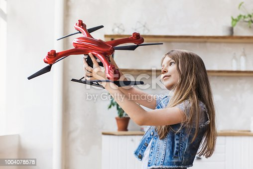 1019302738istockphoto Little girl child with drone at home 1004078578