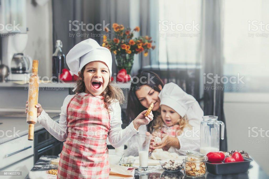 Niño niña con el cocinero feliz madre y hermana en la mesa de la cocina es encantador y hermoso - foto de stock