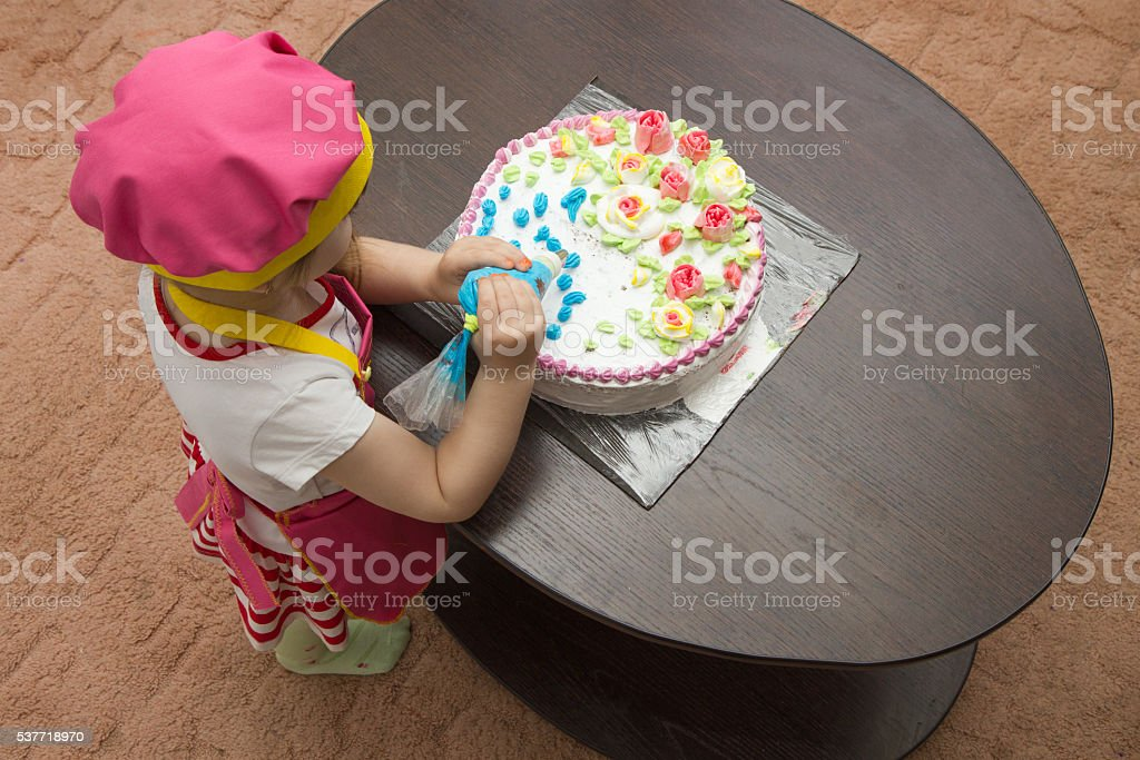 Little girl children decorate cream cake Little girl children decorate cream cake on table Apron Stock Photo