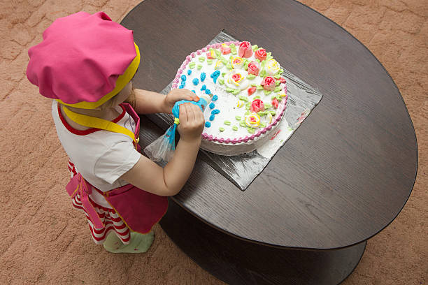 Little girl children decorate cream cake Little girl children decorate cream cake on table decorating a cake stock pictures, royalty-free photos & images