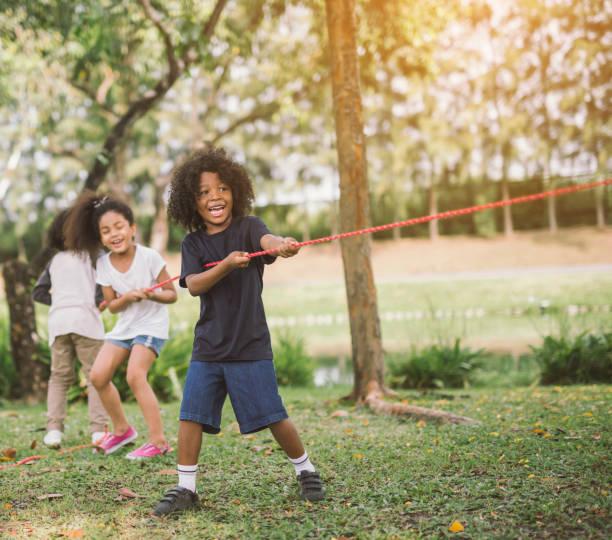 kleine mädchenkinder spielen tauziehen im park - sommerfest kindergarten stock-fotos und bilder