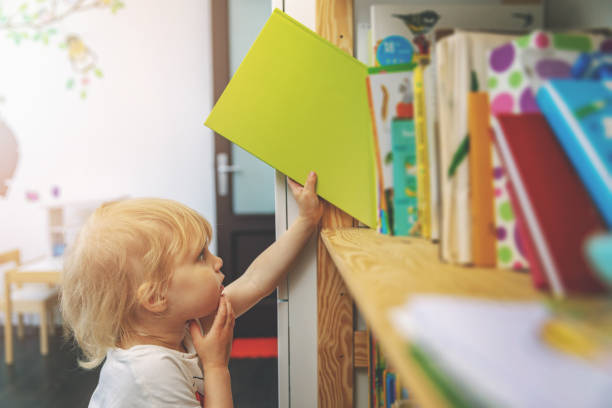 little girl choosing and taking book from shelf to read stock photo