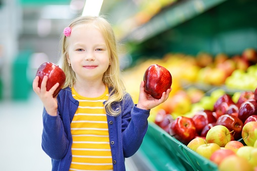 Little girl choosing apples in a food store or a supermarket