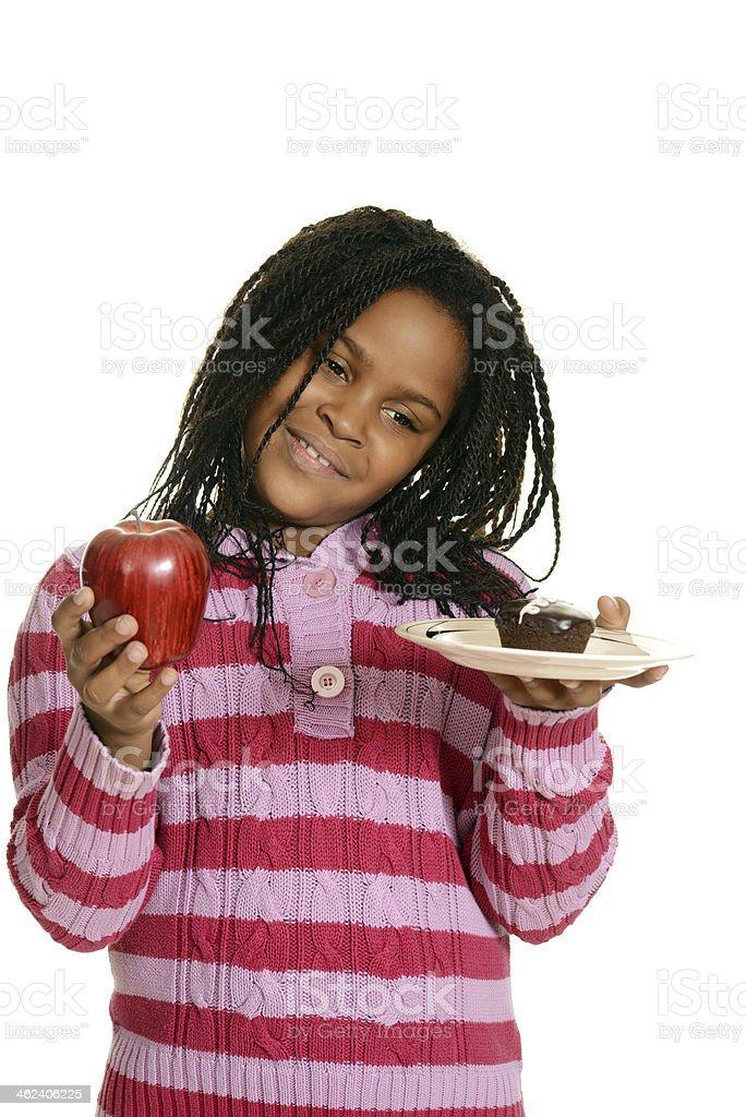 little girl choosing between cupake and apple royalty-free stock photo
