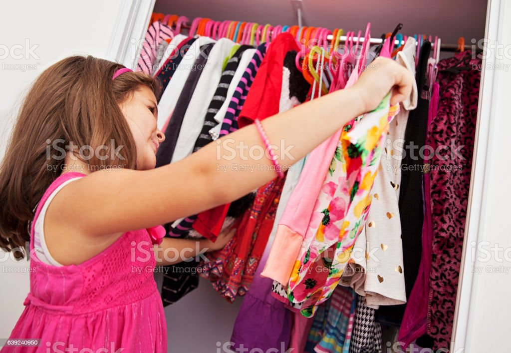 Little girl choosing which dress to wear Little girl choosing which dress to wear Arts Culture and Entertainment Stock Photo