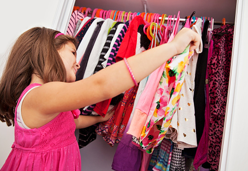 Little Girl Choosing Which Dress To Wear Stock Photo - Download Image Now