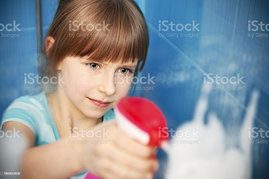 Little girl cleaning a shower window stock photo