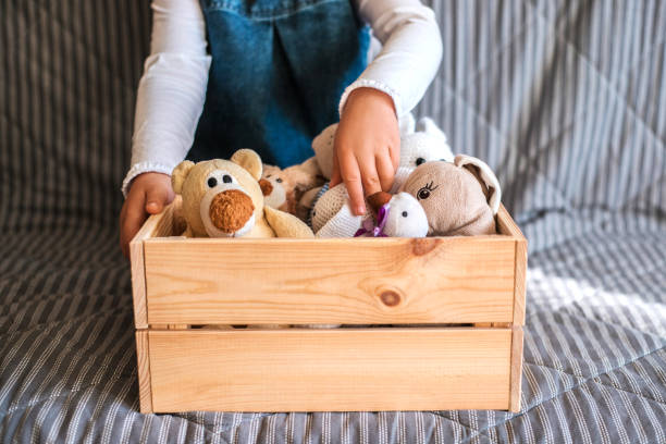 Little girl cleaning up the toy box at home. Little girl cleaning up the toy box at home. Child's space organization. kids cleaning up toys stock pictures, royalty-free photos & images