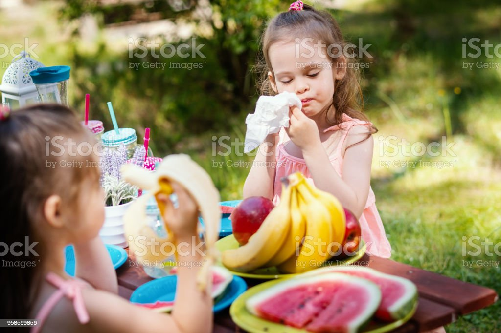 little girl cleans her mouth after eating fruit stock photo