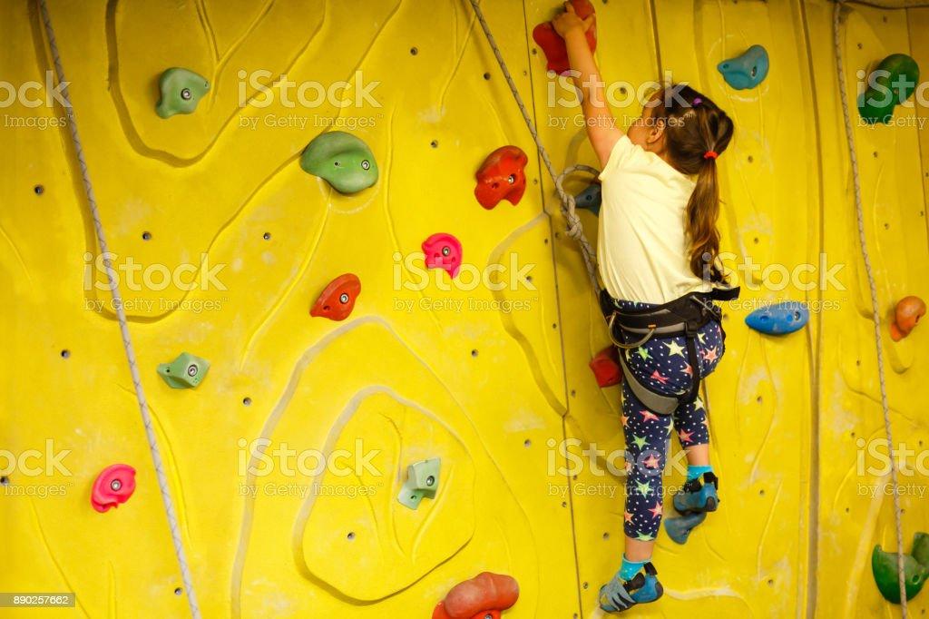 niña, escalar una pared de roca interior - foto de stock