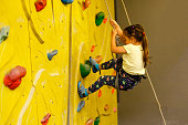 istock little girl climbing a rock wall indoor 890257728
