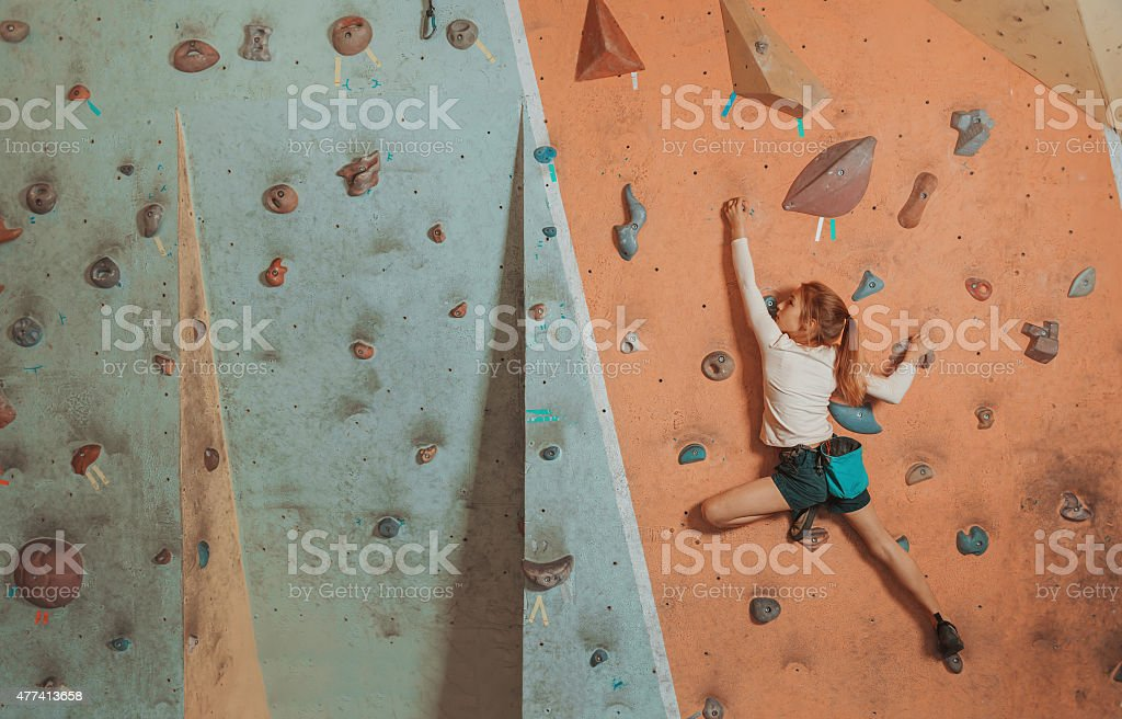 Little girl climbing indoor stock photo