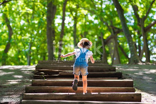 istock Little girl climbing the stairs in the forest 922204270