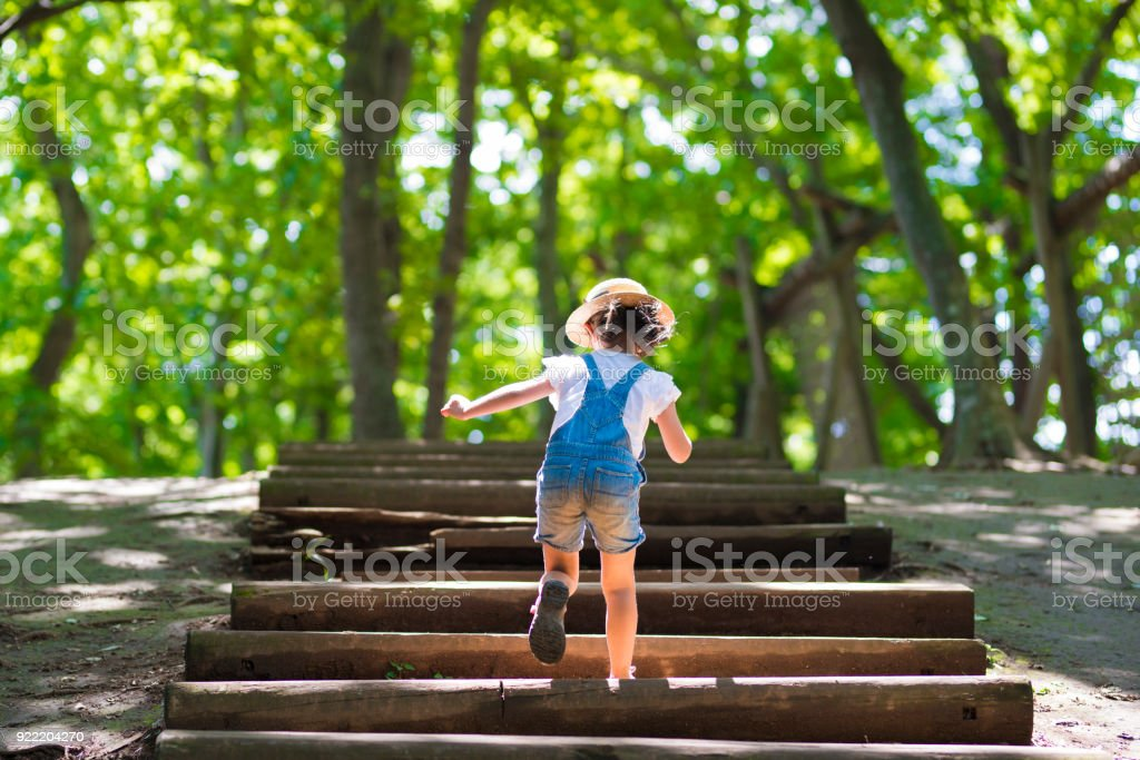 Little girl climbing the stairs in the forest stock photo