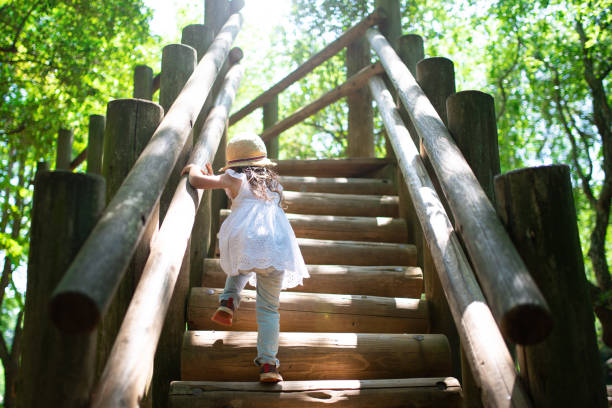 Little girl climbing the stairs in the park stock photo