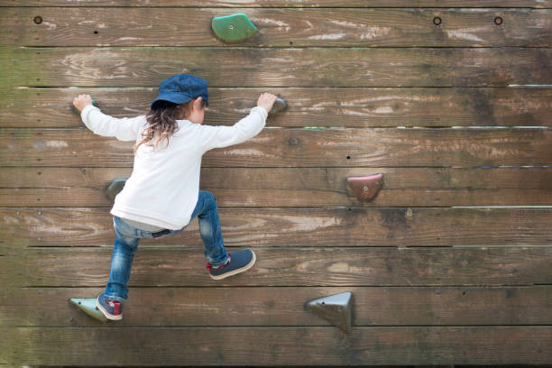 Little girl climbing the wall stock photo