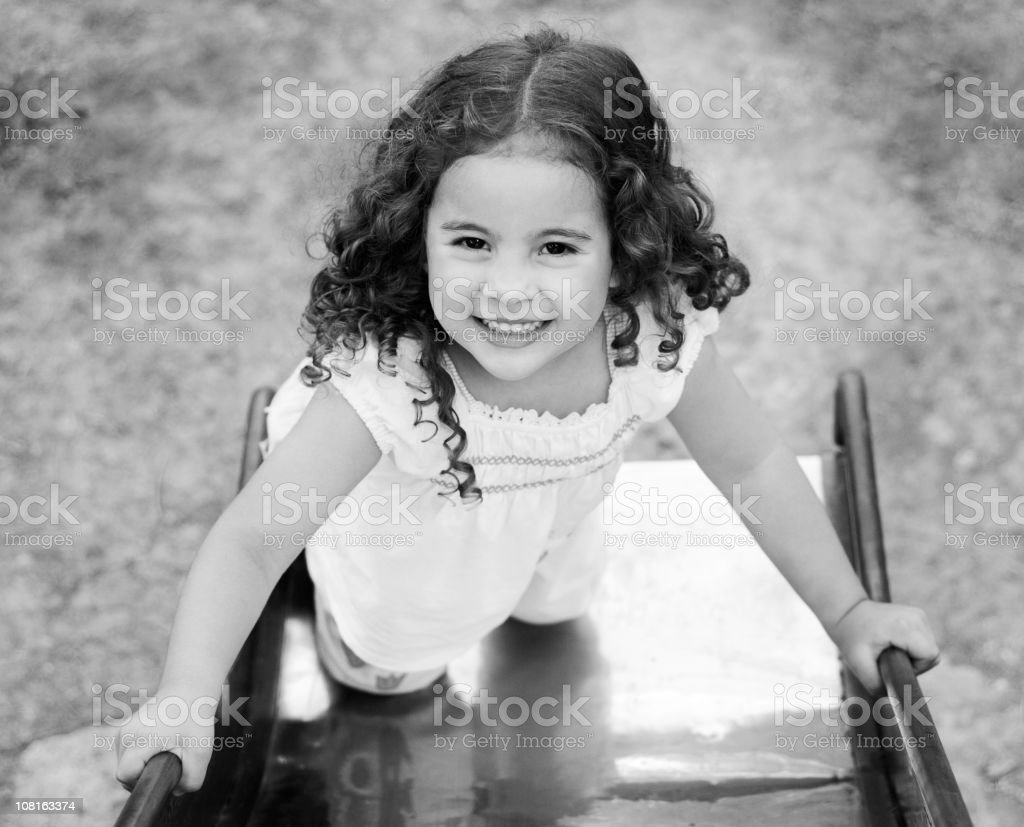 Little Girl Climbing Up Playground Slide, Black and White royalty-free stock photo
