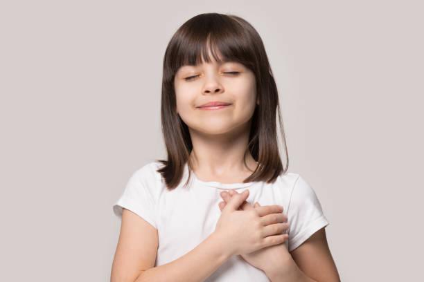 little girl closed eyes hold hand on chest feels gratitude - gratidão imagens e fotografias de stock