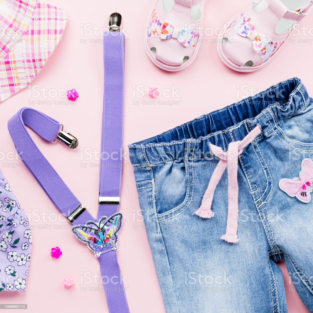 Little girl clothes collection flat lay with floral t-shirt, jeans, sandals on pink background. stock photo