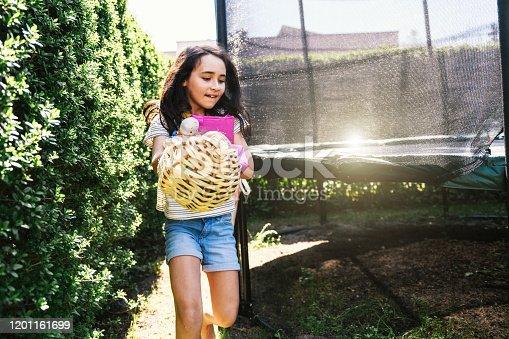 little girl looking in garden for hidden easter eggs