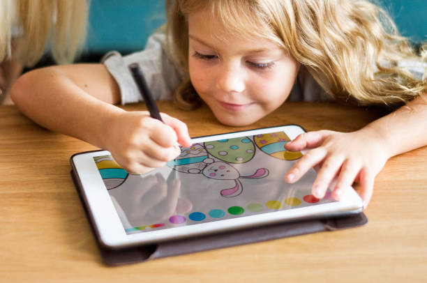 Little girl coloring on a tablet stock photo