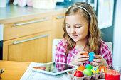 Little girl colors Easter eggs using digital tablet