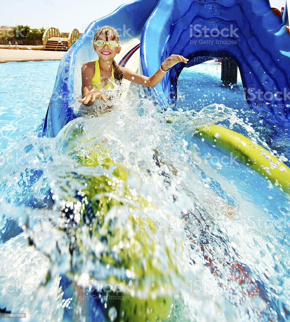 Little girl coming down a water slide stock photo