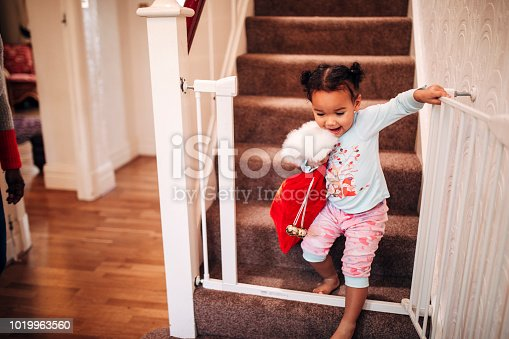 A little girl walks down the stairs on Christmas morning, carrying her stocking about to go see what is left under the tree for her.