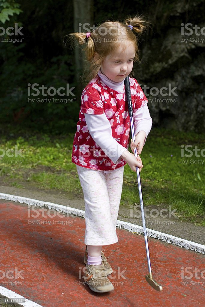 Little girl concentrating for her first game of mini golf royalty-free stock photo