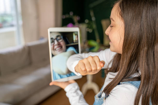 little girl congratulates with digital tablet because of covid-19 stock photo