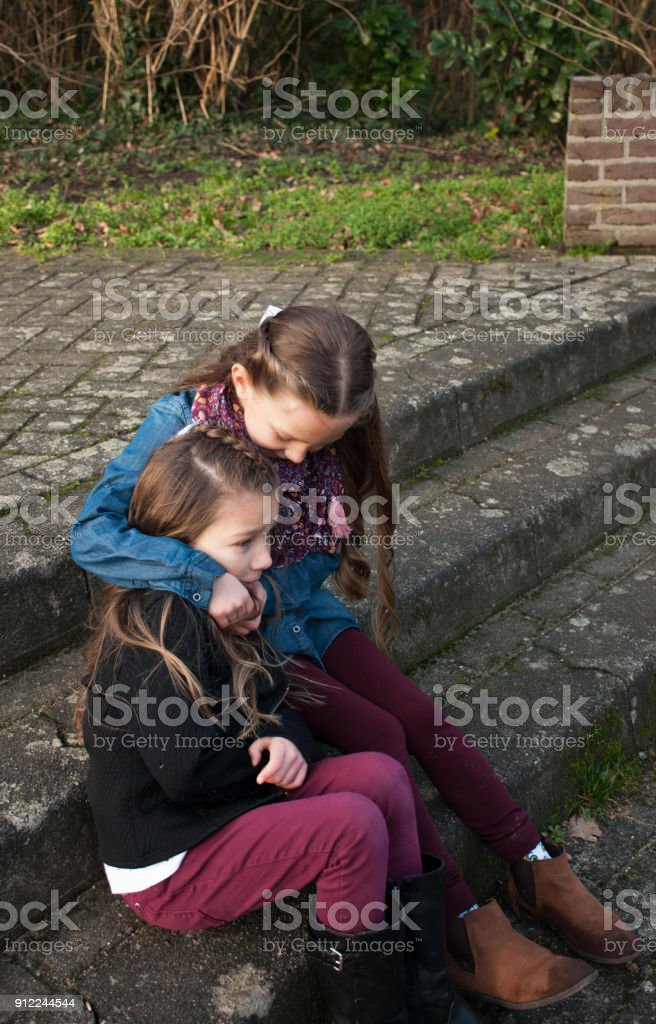 Sad girl sitting on stone steps being consoled by her sister.