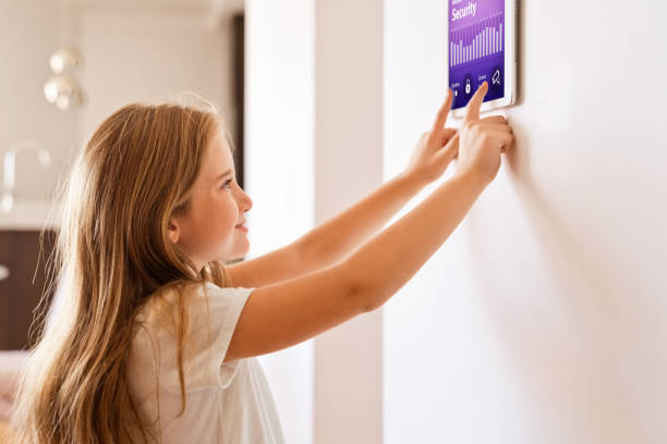 Little girl controlling smart devices with a digital tablet at home Girl controlling home with a digital touch screen panel. Concept of internet of things. smart thermostat stock pictures, royalty-free photos & images