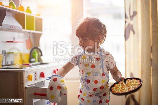 istock Little girl cooking on decorative kitchen at home. 1142678077