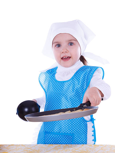 Little girl cooking pancakes stock photo