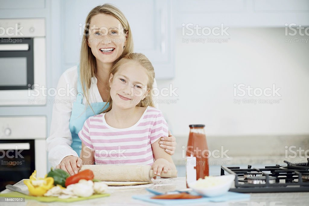 Little girl cooking pizza with mother stock photo