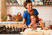Little girl cooking with her mother in the kitchen. Infant Chef Concept.