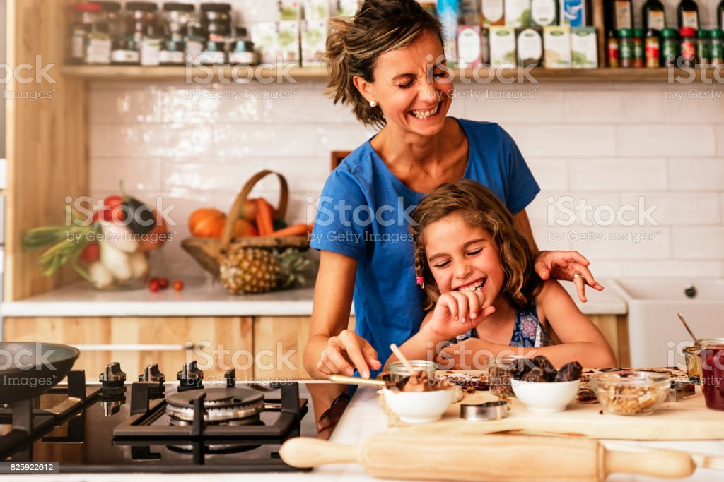 Little girl cooking with her mother in the kitchen. stock photo