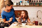 小さな女の子が台所で母親と一緒に料理します。