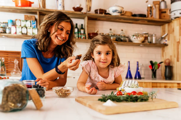 little girl cooking with her mother in the kitchen. - baking bread at home imagens e fotografias de stock