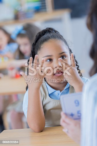 istock Little girl counts on her fingers at school 666835584