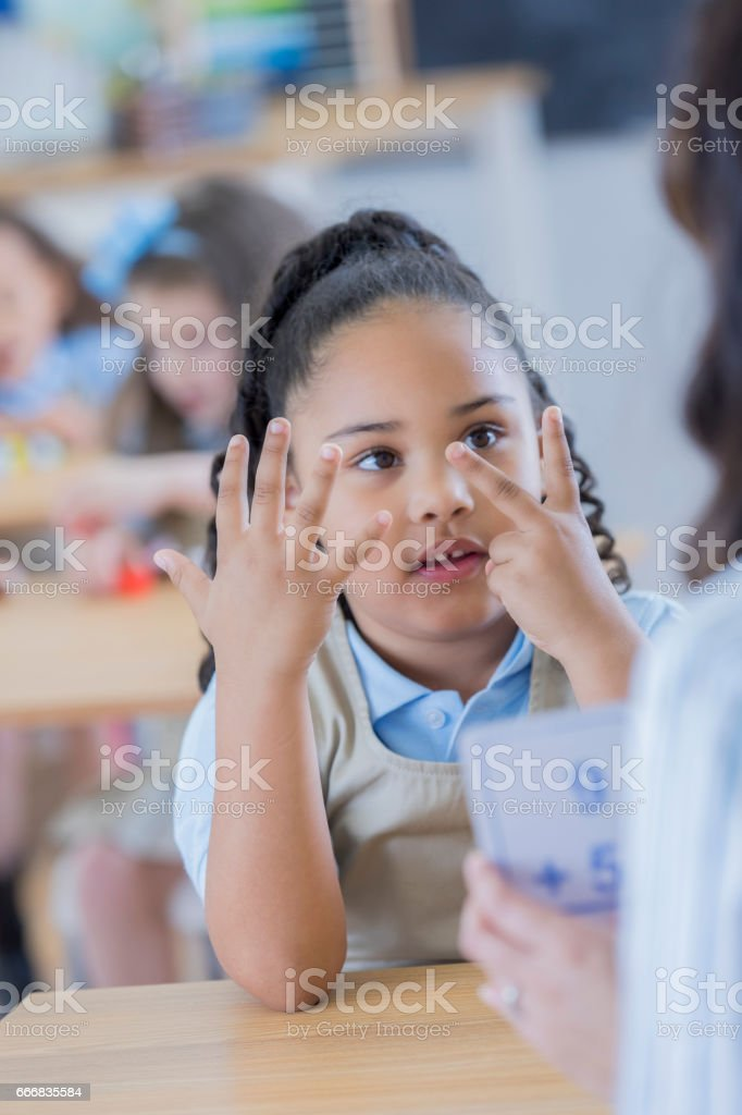 Little girl counts on her fingers at school stock photo