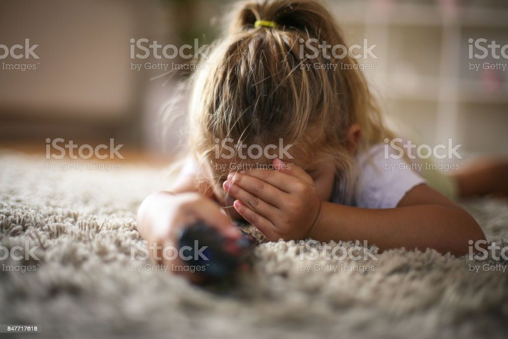 Little girl covered eyes while watching TV. stock photo