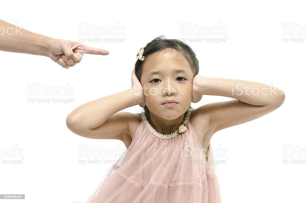 Little girl covering ears while mother scolding stock photo
