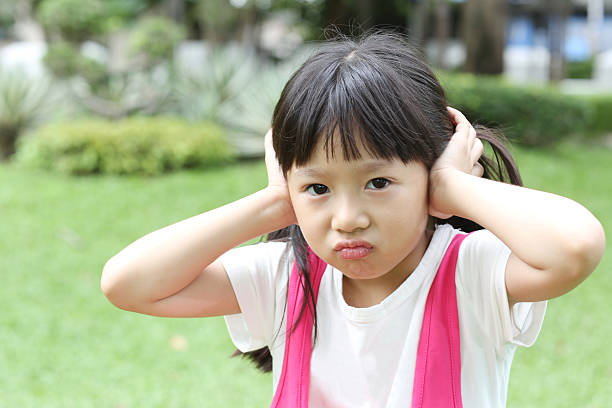 little girl covering her ears. - covering ears stock photos and pictures