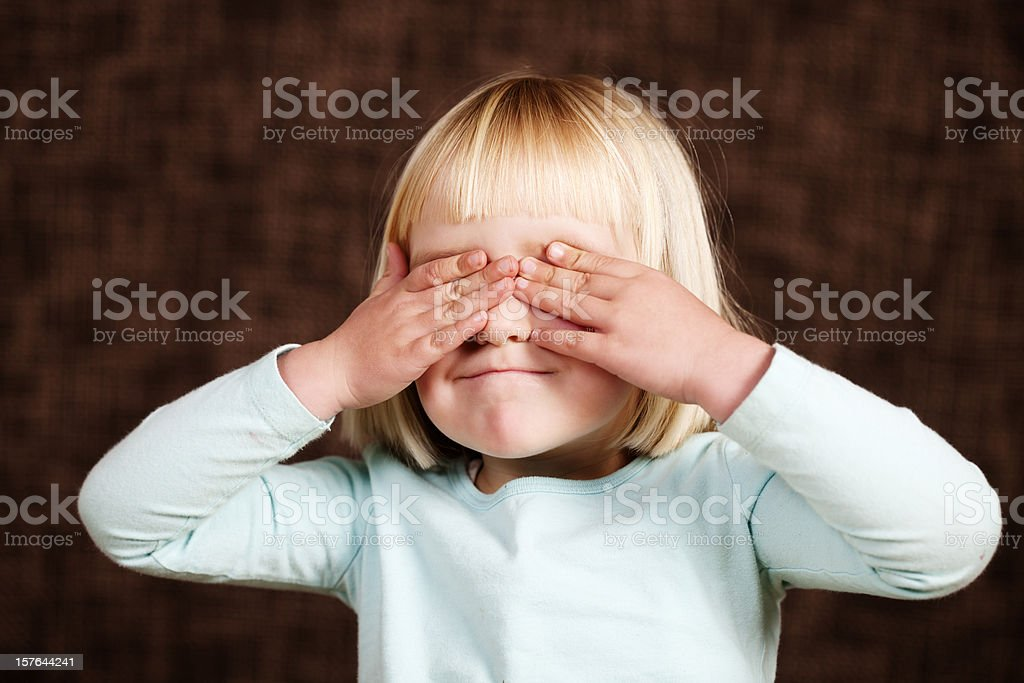 Little girl covers her eyes to