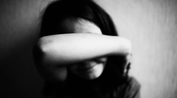 niña se cubre la cara con las manos - human trafficking fotografías e imágenes de stock
