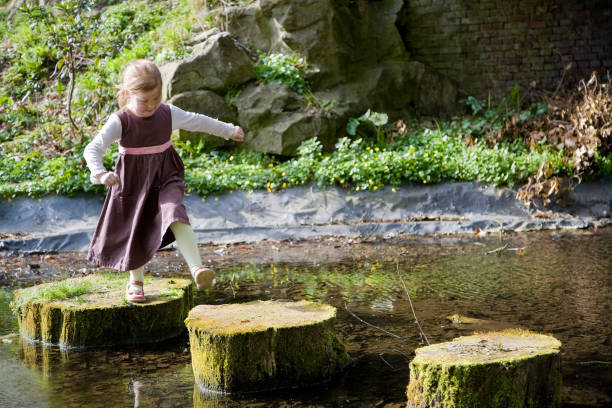 Little girl crossing a pond stock photo