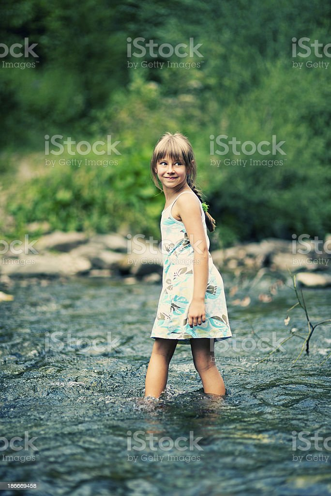 Little girl crossing a river royalty-free stock photo